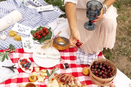 Girl holds juicy ripe cherries in her hand against the background of a checkered picnic blanket with food spread on it.