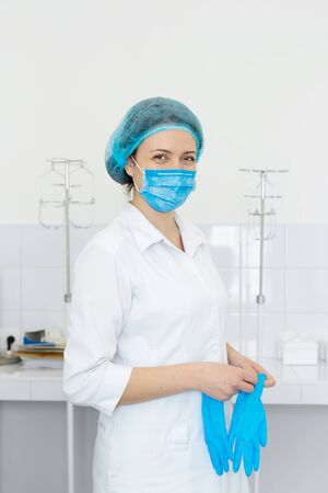 Nurse in scrub and mask puts gloves on her hands. 写真素材