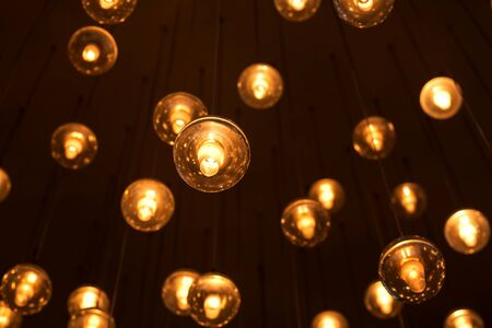 Decorated electric garland for lighting with bulbs warm white and yellow light on a dark background. Blurred background. Bulbs in the interior decor.