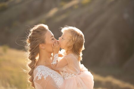Portrait of a beautiful young mom holds her beloved daughter in her arms. Parental love, little princess.