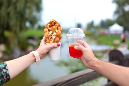 The girl and fella during the walk holds in hands a paper cup with a Belgian waffle and fresh drink
