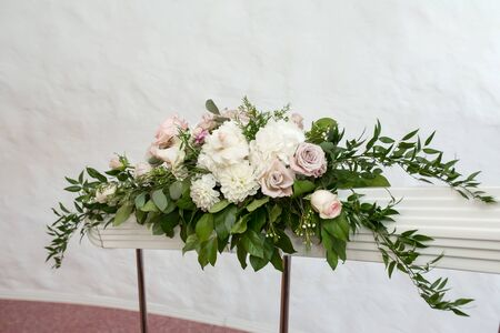 The staircase is decorated with fresh flowers and a plate Wedding. Wedding floristry. The decor of the room at the wedding.