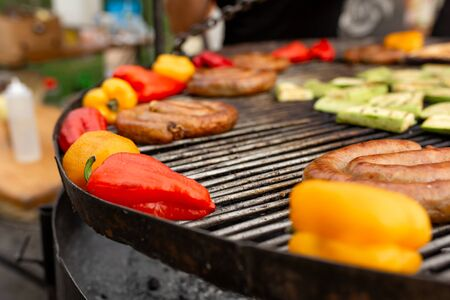 A large round grill on the coals in which grilled color vegetables and fresh meat sausages are cooked. Food and equipment for cooking at a food festival. Фото со стока - 129818115