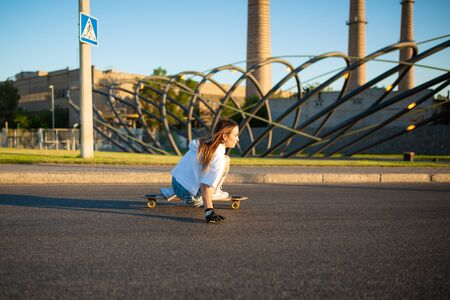 stylish girl in white stockings ride on longboard.