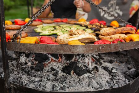 A large round grill on the coals in which grilled color vegetables and fresh meat sousages are cooked. Food and equipment for cooking at a food festival.