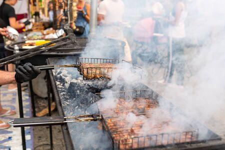 厨师炸薯条在木炭烤架上的多汁蒸肉。食物和烹调设备在街道美食节。