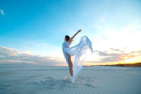 Een meisje in een vliegende witte jurk danst en poseert in de zandwoestijn bij zonsondergang.