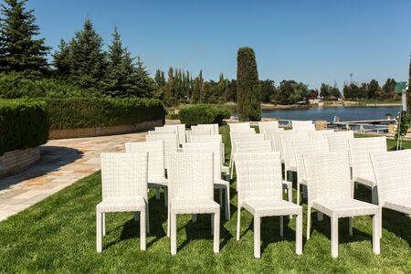 Beautiful outgoing wedding set up.Romantic wedding ceremony , wedding outdoor on the lawn water view. Wedding decor. White wooden chairs on a green lawn. White armchairs for guests.