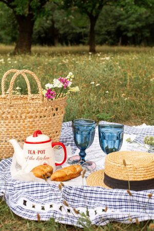 Stylish picnic on the green lawn. Fresh croissants and a teapot with tea on a bedspread near a wicker female hat.