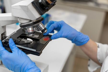 Closeup lab technician research blood sample in microscope Stock Photo