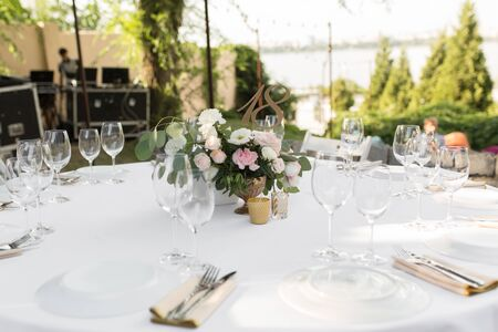 Wedding table setting decorated with fresh flowers in a brass vase. Wedding floristry. Banquet table for guests outdoors with a view of green nature. Bouquet with roses, eustoma and eucalyptus leaves.