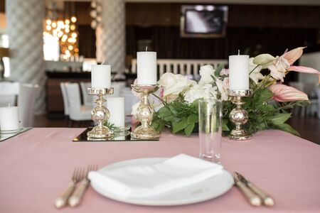 The wedding table setting for the newlyweds is decorated with fresh flowers of carnation, rose, anthurium and eucalyptus leaves. Silver candlesticks, white candles. Wedding floristry. Closeup details.