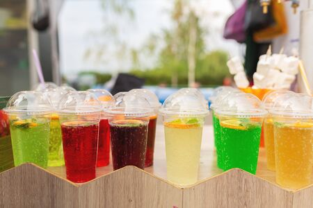A counter with multi-colored fruit cocktails in plastic cups. Food and cooking equipment at a street food festival.