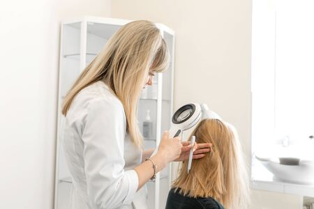 The doctor trichologist dermatologist examines the scalp and the patients hair condition with a dermatoscope.