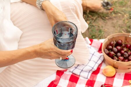 woman drink water from glass at outdoor picnic on green lawn.