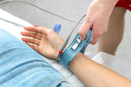 The therapist connects the electrocardiograph sensors to the patients hand. Stock Photo