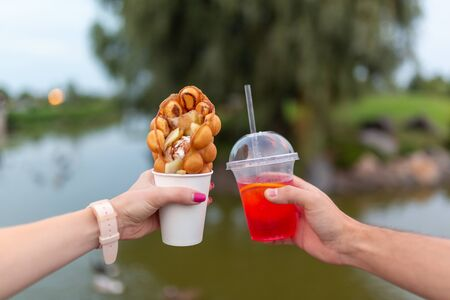 girl and fella during the walk holds in hands a paper cup with a Belgian waffle and fresh drink on a background of green park.