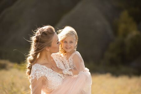 Portrait of a beautiful young mom holds her beloved daughter in her arms. Parental love, little princess. Reklamní fotografie - 130716036