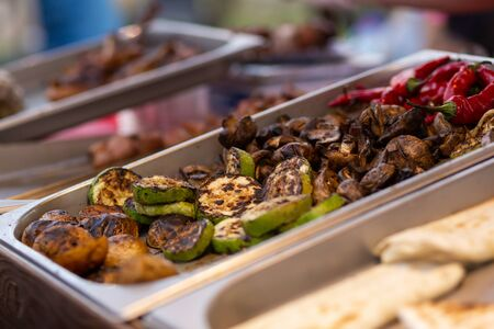 A counter with metal trays containing grilled food. Food and cooking equipment at a street food festival.