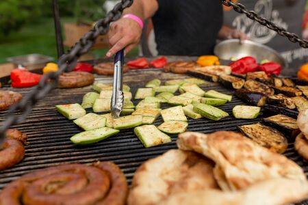 A large round grill on the coals in which grilled color vegetables and fresh meat sausages are cooked. Food and equipment for cooking at a food festival.