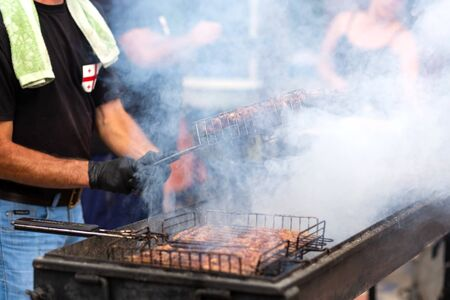 The cook fries juicy steaming meat on a charcoal grill. Food and cooking equipment at a street food festival. Stock Photo