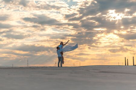 Romantic couple dancing in sand desert. The guy lifts the girl above himself. Sunset sky