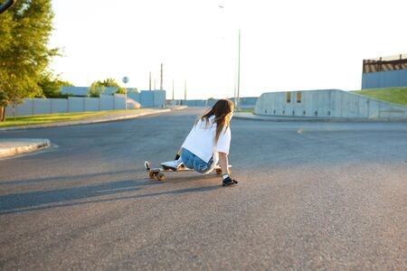 Young girl having fun with skateboard on the road. Young woman skating on a sunny day.