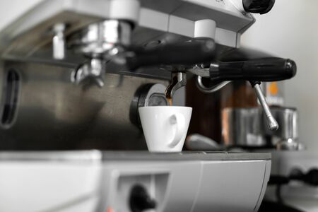 A coffee machine pours freshly brewed hot coffee into a white cup.