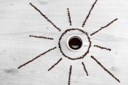 Coffee grains folded in the form of the sun on a wooden background. In the middle is a cup of coffee, meaning its time to drink coffee after sunrise. Banco de Imagens