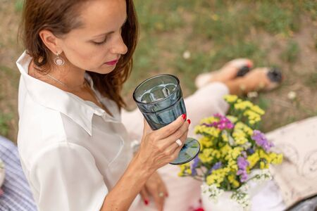 woman drink water from glass at outdoor picnic on green lawn Stock Photo