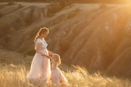 Mom with daughter in pink fabulous dresses in nature, holding hands. Sunset sun rays.