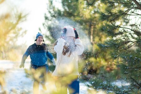 Loving couple play snowballs in winter in the forest. The guy sculpts and throws snowballs at the girl. Laugh and have a good time.