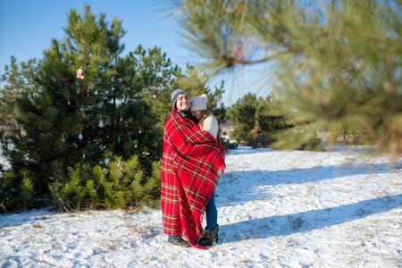 Winter walk through the woods. The guy in the red plaid blanket wraps the girl up so she gets warm.