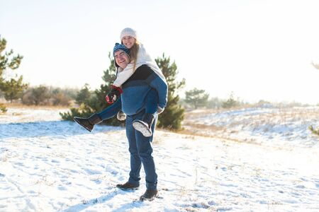Loving couple play in the winter in the forest. Girl rides a guy in the background of the Christmas tree. Laugh and have a good time. Zdjęcie Seryjne