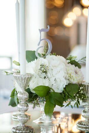 Nakrycie weselne ozdobione jest świeżymi kwiatami i białymi świecami. Florystyka ślubna. Bukiet z róż, hortensji i eustomy. Na tle rozmycia płoną girlandy z żarówkami. Zdjęcie Seryjne