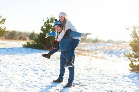 Loving couple play in the winter in the forest. Girl rides a guy in the background of the Christmas tree. Laugh and have a good time. Stock fotó