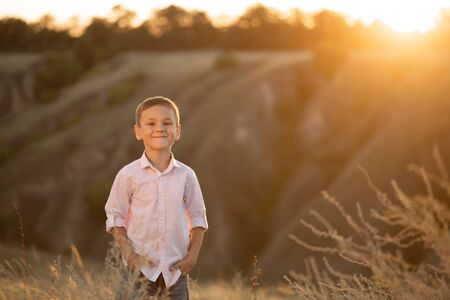 Stylish young boy posing in field at sunset.