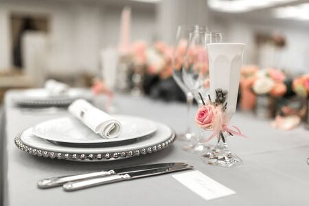 Part of stylish table setting with plate and cutlery. Nearby lies a white business card. Copy space.