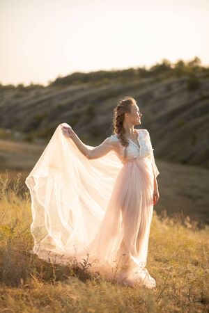 Young gorgeous woman in air pink dress posing in the field. 写真素材