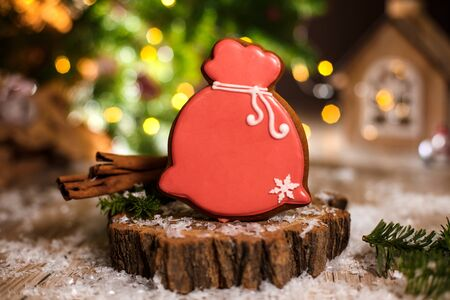 Holiday traditional food bakery. Gingerbread santa claus bag of christmas gifts in cozy warm decoration with garland lights.