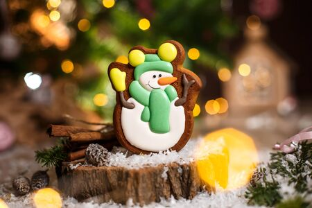 Holiday traditional food bakery. Gingerbread happy snowman in hat and scarf in cozy decoration with garland lights.