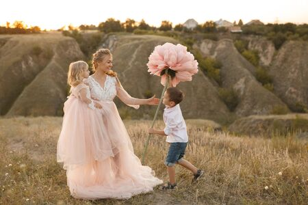 Stylish young boy gives a big flower to his mom in a field at sunset. Archivio Fotografico