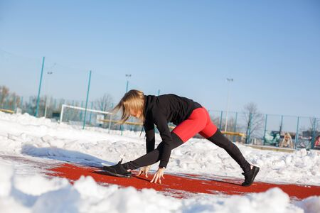 Young caucasian female blonde in violet leggings stretching exercise on a red running track in a snowy stadium. fit and sports lifestyle.