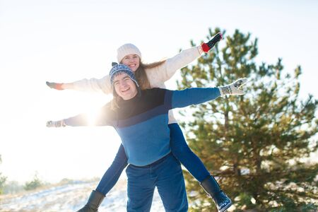 Loving couple play in the winter in the forest. Girl rides a guy in the background of the Christmas tree. Laugh and have a good time. Stock Photo