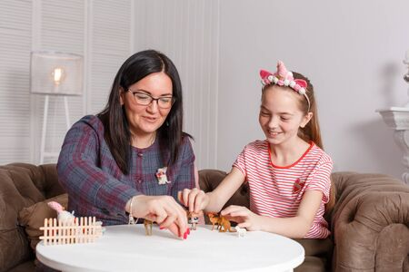 professional child psychologist with a teenage girl. Disclosing a child through a game with animal toy figures. The method of work of a child psychotherapist.