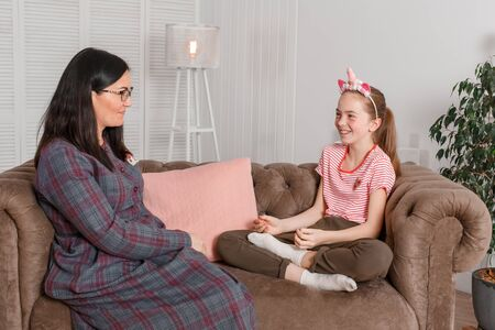 professional child psychologist with a teenage girl. Teen girl tells a story with a smile on her face. The method of work of a child psychotherapist.