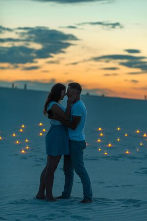 Couple in love romantic hugs in sand desert. Evening, romantic atmosphere, in sand burn candles.