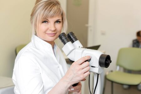 Portrait of a smiling female blond doctor gynecologist near colposcope. Examination by a gynecologist. Female health concept. Stock Photo