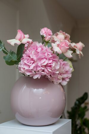 Wedding decorations. Holiday decoration vase with fresh flowers. Pink roses and carnations 스톡 콘텐츠