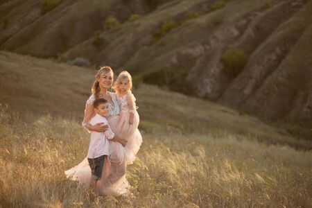A young mother with children walks in a field at sunset. Country style. Reklamní fotografie - 132233212